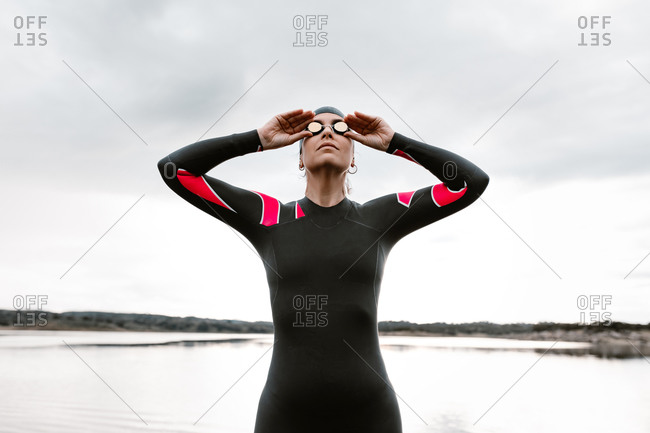 Low angle of confident adult woman in diving suit and goggles with cap standing against gloomy lake