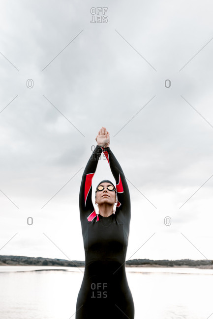 Low angle of confident adult woman in diving suit and goggles with cap standing against gloomy lake preparing to swim