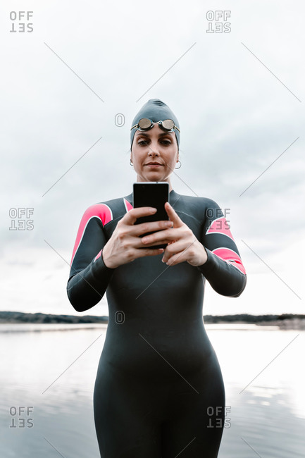 Smiling woman in diving suit and cap using phone and taking selfie while standing on shore of lake