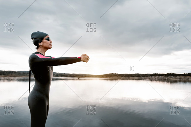 Side view slim barefoot female in black wetsuit warming up shoulder joints while stretching arms aside standing on peaceful shore of lake in overcast