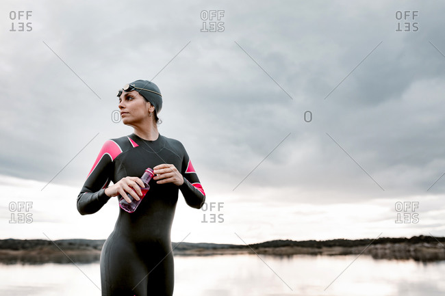 Calm pensive sportswoman in wetsuit and cap having drink in bottle standing on peaceful lake shore with clouds