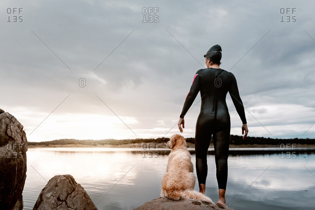 Back view of anonymous woman in black wetsuit standing with dog on stone looking away while observing lake nature