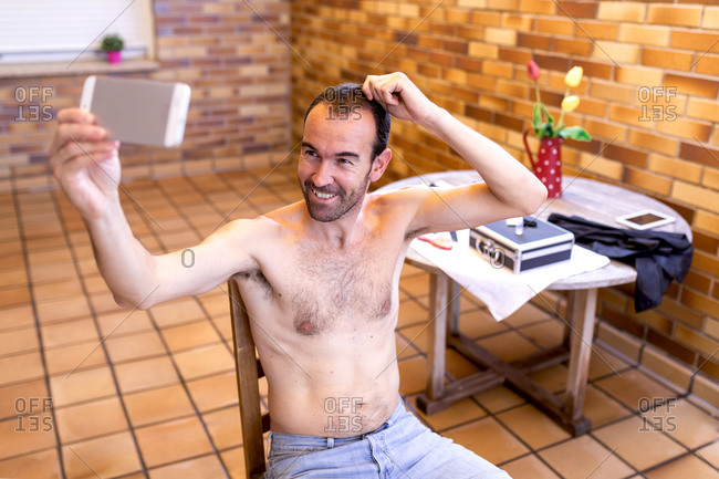 Glad shirtless man in jeans taking selfie on cellphone while touching hair and sitting on wooden stool in barbershop with brick wall and ceramic floor