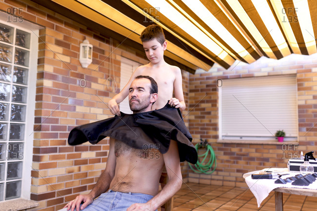 Serene shirtless teenager putting black wavy cape on adult father in jeans while sitting on stool in hairdressing salon near table with accessories