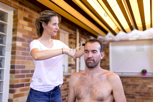 Smiling hairdresser in t shirt using plastic comb and scissors while trimming hair to male at home