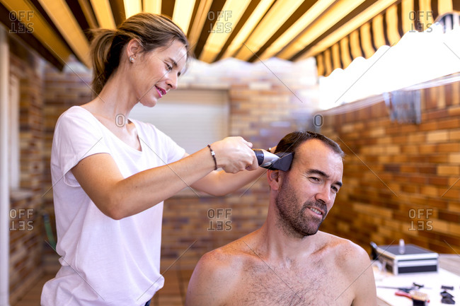 Positive female barber in t shirt using trimmer while doing haircut to shirtless masculine bearded client in hairdressing salon with brick wall