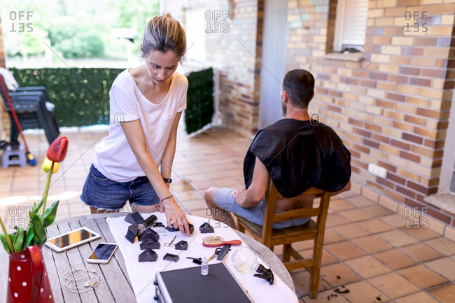 Slim female in denim shorts taking trimmer nozzle while standing near table with gadgets and accessories before cutting hair to man in cape