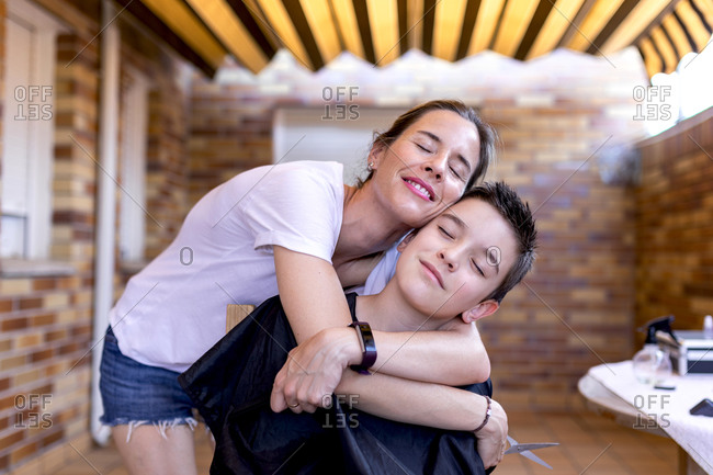 Adult female barber in casual wear and smart watch holding scissors while cuddling teenager with closed eyes in hairdressing salon with brick wall