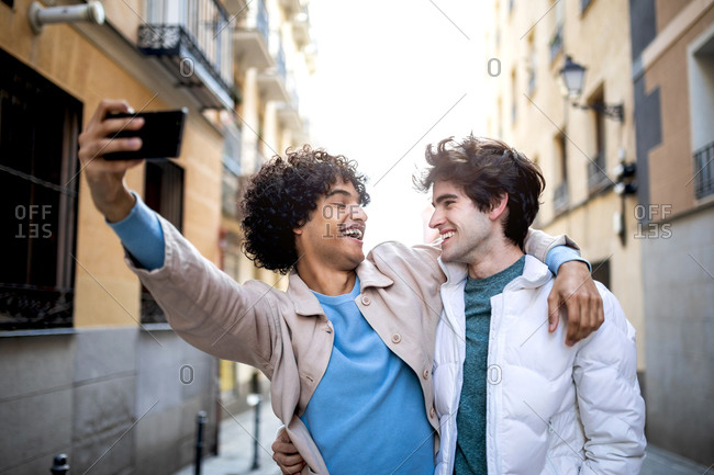 Multiethnic homosexual couple hugging on street and taking photo on mobile phone while looking at each other