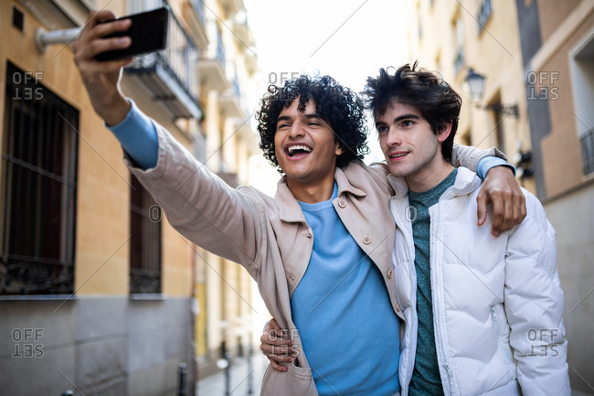 Multiethnic homosexual couple hugging on street and taking photo on mobile phone