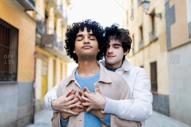 Multiracial gay couple in stylish clothes embracing while enjoying city stroll together