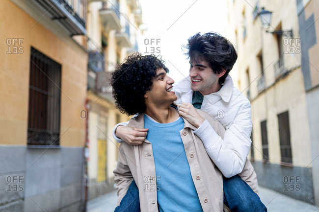 Smiling ethnic man in stylish wear piggybacking delighted boyfriend during city stroll