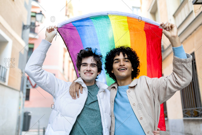 Content multiethnic homosexual couple embracing on street while standing with rainbow flag
