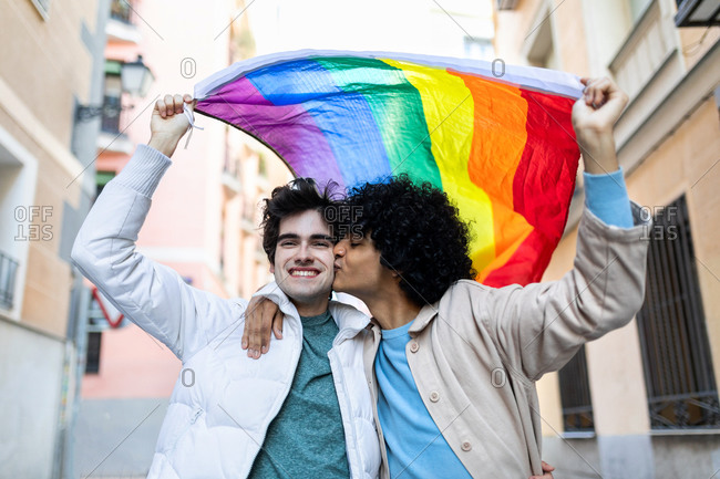 Content multiethnic homosexual couple kissing on street while standing with rainbow flag