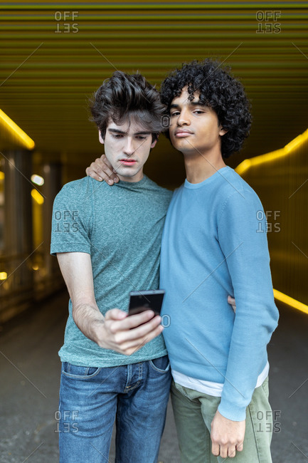 Loving multiethnic homosexual couple in trendy clothes embracing on street and taking photo on mobile phone camera