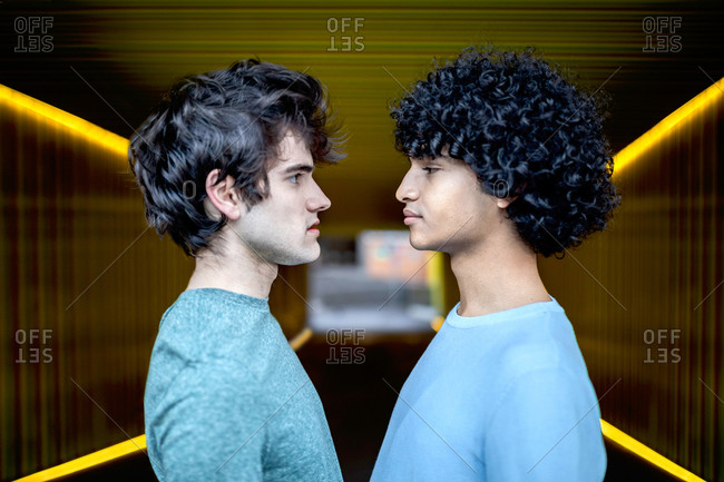 Serious multiracial gay couple standing in illuminated passage in city looking at each other