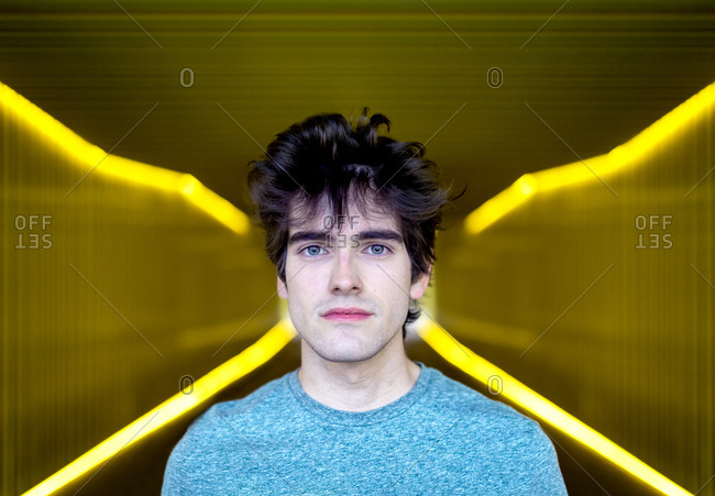 Young handsome male with blue eyes standing in illuminated walkway in city and looking at camera