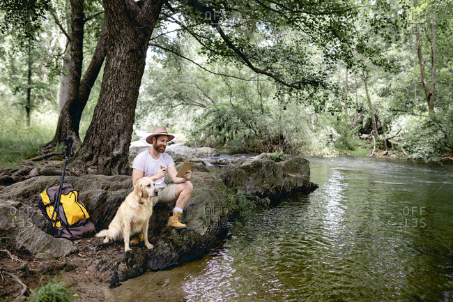 young man in a hat and yellow backpack sitting in the shade on the shore of a tree-filled lake lounging with his beige dog after hiking