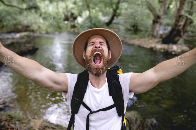 young man with beard hat on his head and yellow backpack hiking down a lake route with trees and shady areas taking a selfie
