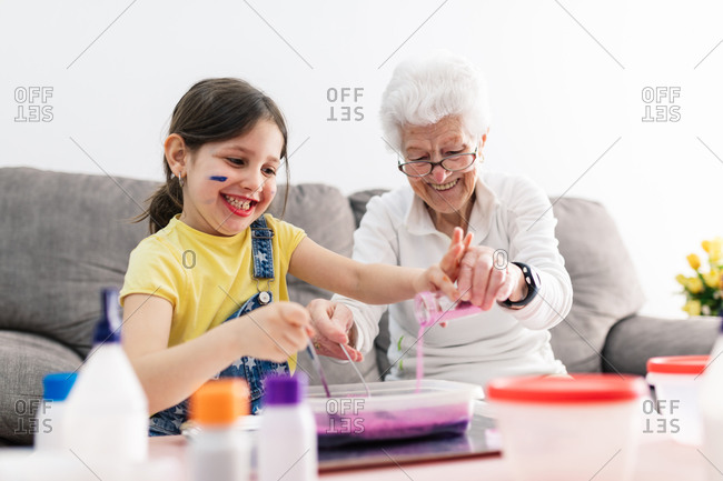 Smiling granny in eyeglasses helping positive granddaughter with dirty face in casual wear preparing blend using colorants in plastic container while sitting on comfortable couch in living room
