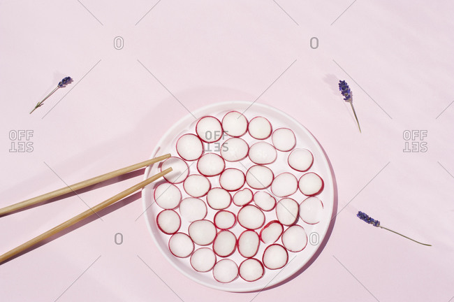 Top view of circles of fresh radish placed on plate with wooden chopsticks and lavender flowers