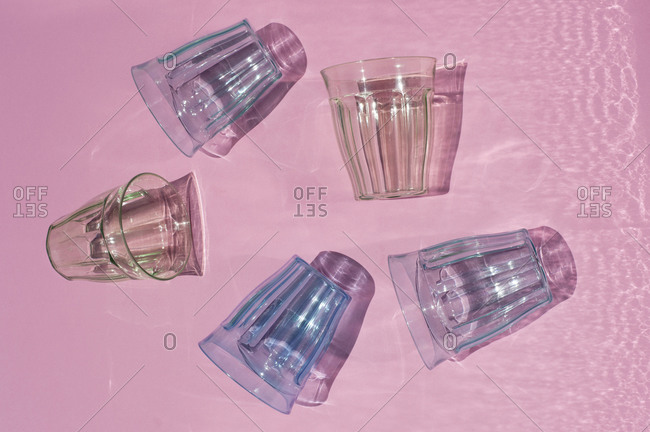 From above of assorted colorful glassware casting shadow placed on pink background in studio