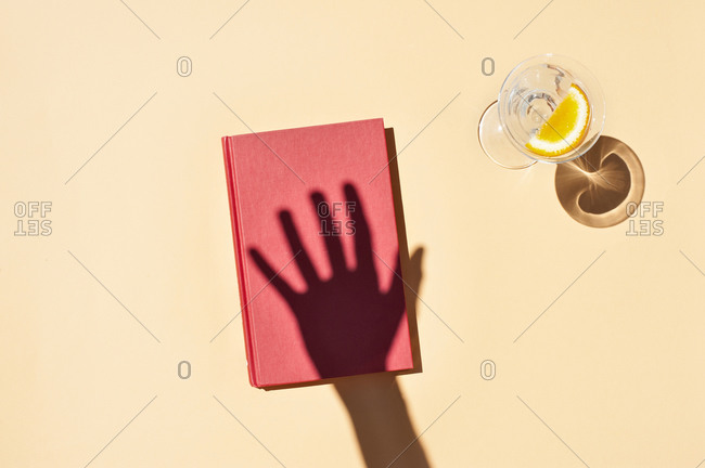 Top view of shadow of hand of anonymous person on notepad placed on pink surface near glass of water with slice of orange