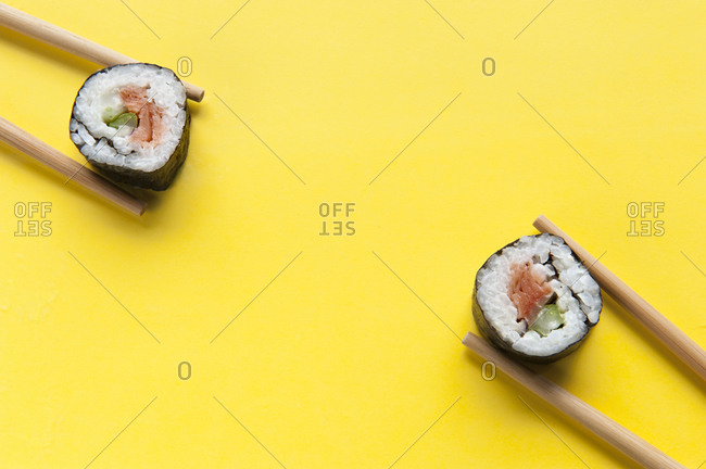 Top view of delicious rolls with rice and salmon placed on colorful yellow table with chopsticks in studio