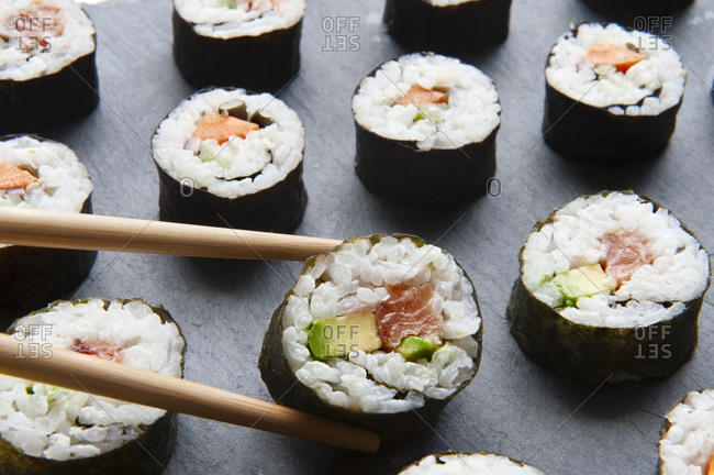 Delicious rolls with rice and salmon placed on a slate board with chopsticks in studio