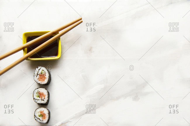 Top view of delectable rolls with salmon and avocado placed on table with soy sauce and chopsticks