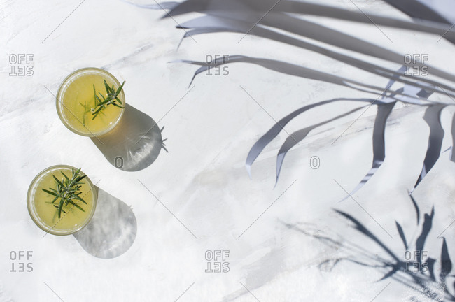 From above of glasses with citrus juice garnished with sprig of rosemary and placed on white marble table on sunny day