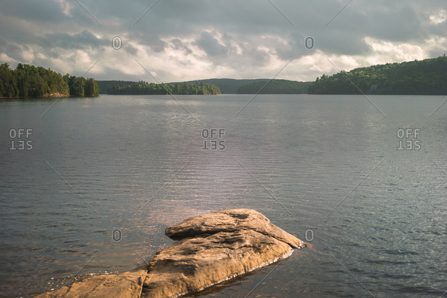 Stony shore near calm lake in cloudy summer day in Algonquin Provincial Park in Canada