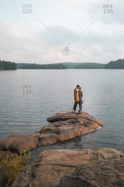 Side view of loving couple tenderly kissing on background of picturesque lake in Algonquin Provincial Park in Canada