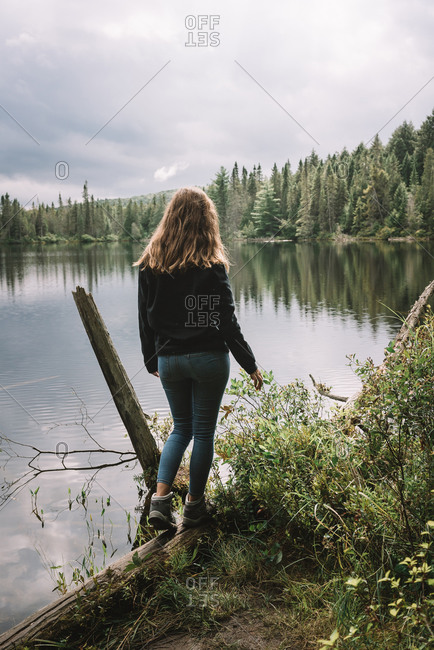 Back view of unrecognizable female tourist in casual outfit standing on lake shore surrounded by green forest and enjoying freedom and nature in overcast weather in Algonquin Provincial Park in Canada