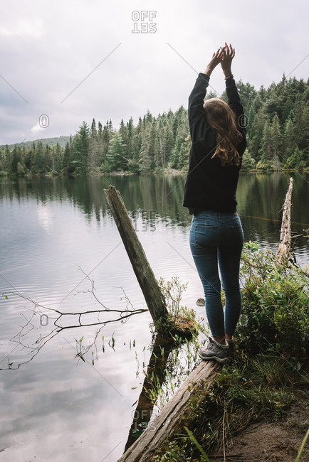 Back view of unrecognizable female tourist in casual outfit standing with arms raised on lake shore surrounded by green forest and enjoying freedom and nature in overcast weather in Algonquin Provincial Park in Canada