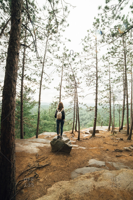 Full length back view of unrecognizable female backpacker walking on rocky mountain slope against green forest in cloudy day in Algonquin Provincial Park in Canada