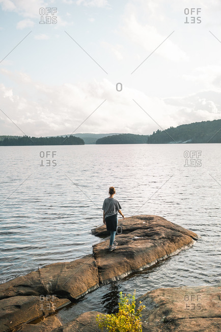 Back view of anonymous male hiker standing on stony shore near calm lake and enjoying freedom during cloudy summer day in Algonquin Provincial Park in Canada