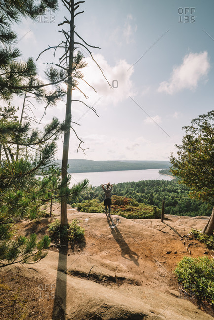 Back view of unrecognizable female walking on rocky mountain slope against green forest near lake in cloudy day in Algonquin Provincial Park in Canada