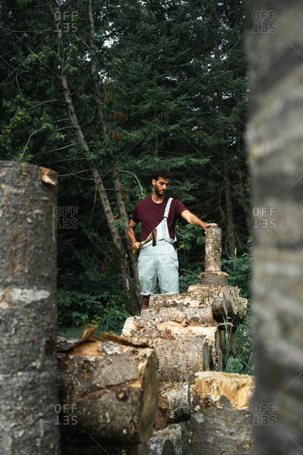 Adult male traveler cutting woods standing against lush dark woods in New Brunswick