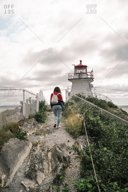 Back view of unrecognizable female traveler walking on rocky path towards Peggys Cove Lighthouse against cloudy sky on seashore in Canada