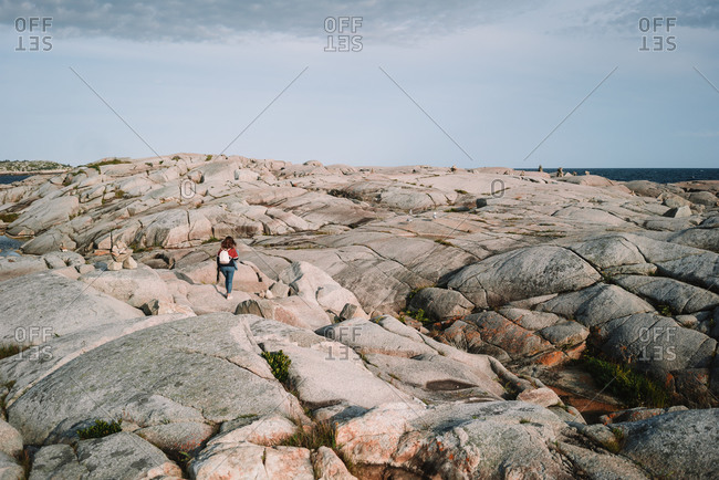 Back view of anonymous female tourist walking on rough stony coast against gray cloudy sky near sea in Peggys Cove, Canada
