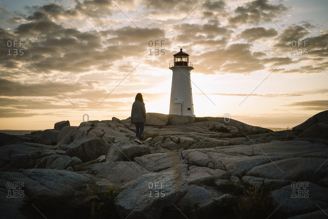 Back view of anonymous woman standing on stony path and looking at Peggys Cove Lighthouse against cloudy sundown sky in Canada