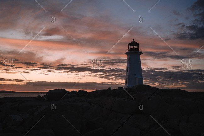 Peggys Cove Lighthouse located on stony coast against sea and cloudy sunset sky in evening in Canada