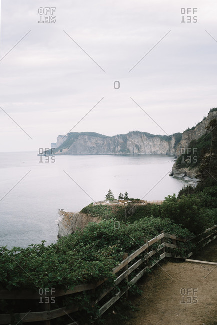 Walking trail overlooking the ocean shore with cliffs in the distance