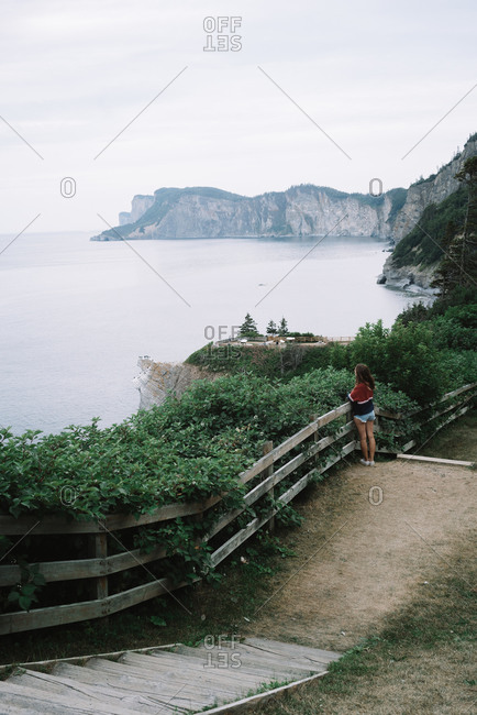 Woman at distance standing at fence against ocean landscape with huge cliffs in haze