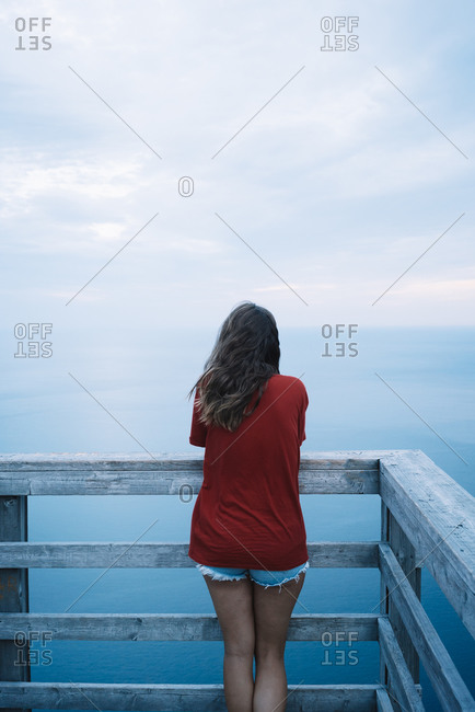 Back view of hipster woman while standing on wooden observation deck against ocean shore
