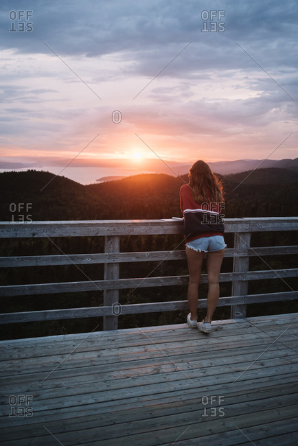 Back view of hipster woman while standing on wooden observation deck at sunset