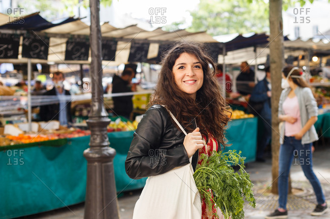 Side view of happy female with eco friendly shopping bag with fresh vegetables shopping on local marker while looking at camera