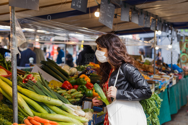 Side view of calm female wearing face protective mask with eco friendly shopping bag choosing fresh vegetables on local marker