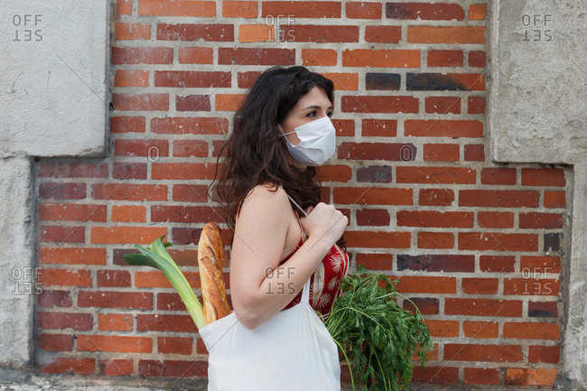 Side view of female wearing protective mask standing with reusable shopping bag full of groceries during coronavirus epidemic